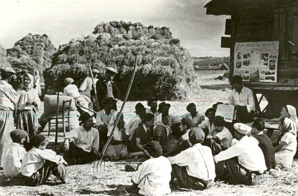 Peasants on a collective farm in Livezeni village, Arge? County being read a newspaper in 1950